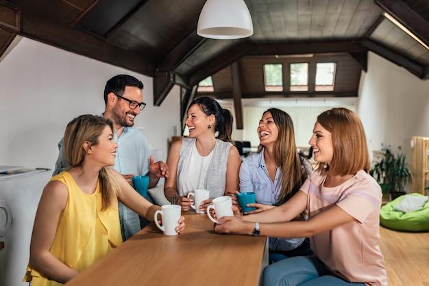 Cinco colegas de trabalho rindo enquanto na pausa no espaço de coworking moderno.