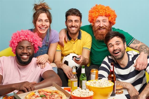 Cinco companheiros alegres sorriem amplamente, expressam emoções positivas, alegria, observam o jogo esportivo, seguram o atributo do futebol e riem de bom grado enquanto o time favorito ganha o oponente, comem pipoca e bebem cerveja