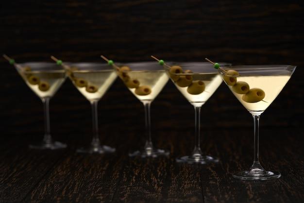 Cinco copos de bebida alcoólica em uma mesa preta
