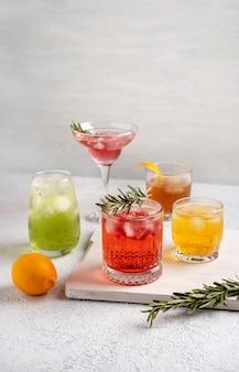Cinco coquetéis coloridos de verão em copos na mesa branca