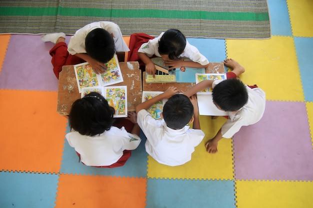 Cinco crianças de alunos do ensino fundamental estão lendo histórias de histórias em quadrinhos na biblioteca da escola.