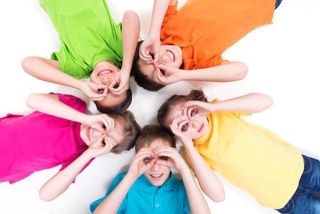 Cinco crianças felizes, deitadas no chão em um círculo com as mãos perto dos olhos em camisetas brilhantes. vista do topo. isolado no branco.