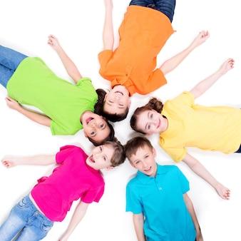 Cinco crianças sorridentes deitadas no chão em um círculo em camisetas brilhantes. vista do topo. isolado no branco.