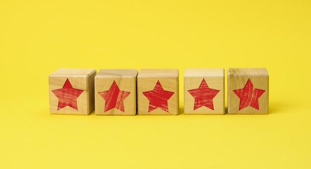 Cinco cubos de madeira com uma estrela vermelha em uma superfície amarela
