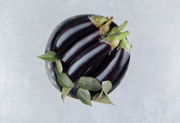 Cinco deliciosas berinjelas na tigela na superfície branca