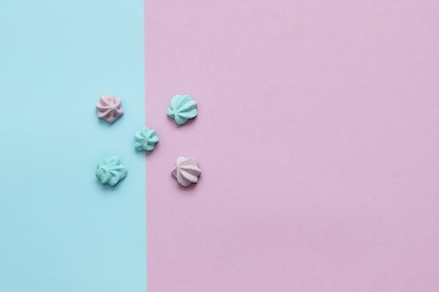 Cinco doces de azul suave e lilás estão dispostos no fundo das mesmas cores. proporção de um a três. fechar-se. vista do topo.