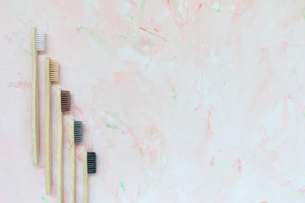 Cinco escovas de dentes de bambu de madeira naturais diferentes. conceito de plástico livre e zero desperdício. vista superior, fundo rosa, cópia espaço