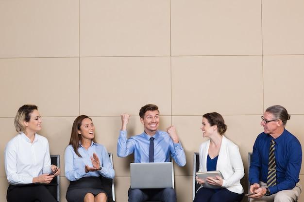 Cinco executivos alegres na sala de espera