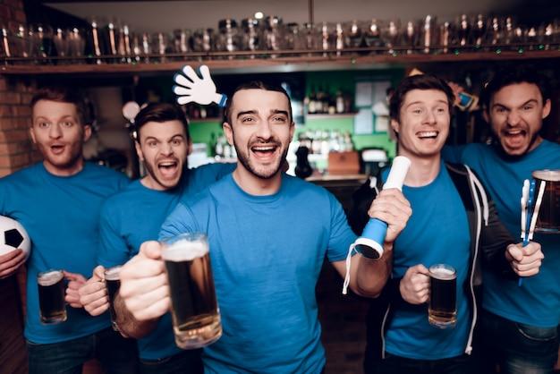 Cinco fãs de esportes bebendo cerveja no bar de esportes