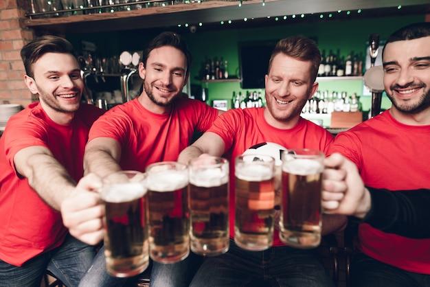 Cinco fãs de esportes bebendo cerveja no bar.