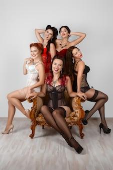 Cinco garotas de espartilho e lingerie posando perto de poltrona.