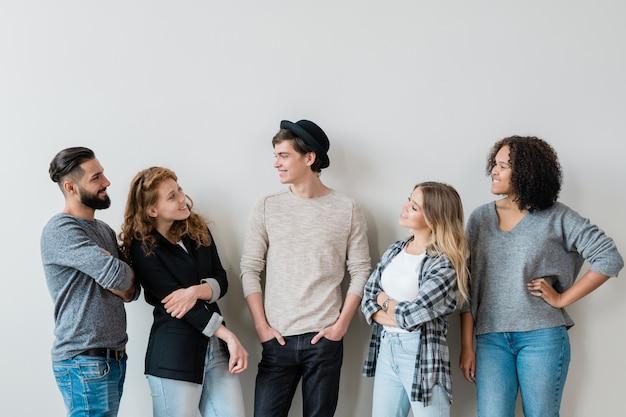 Cinco garotos e garotas despreocupados e casuais conversando amistosamente em pé contra uma parede branca no estúdio