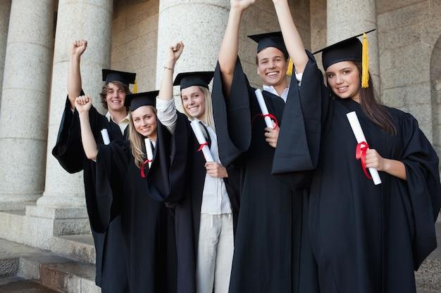Cinco graduados felizes posando o braço levantado
