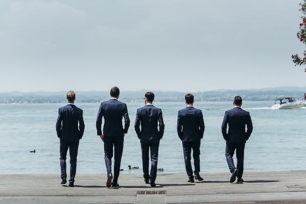 Cinco homens de terno elegante caminham em direção ao mar azul