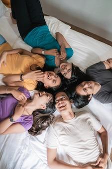 Cinco jovem amigo asiático se divertindo juntos no quarto, filmado de cima enquanto eles estão deitados na cama com as cabeças juntas