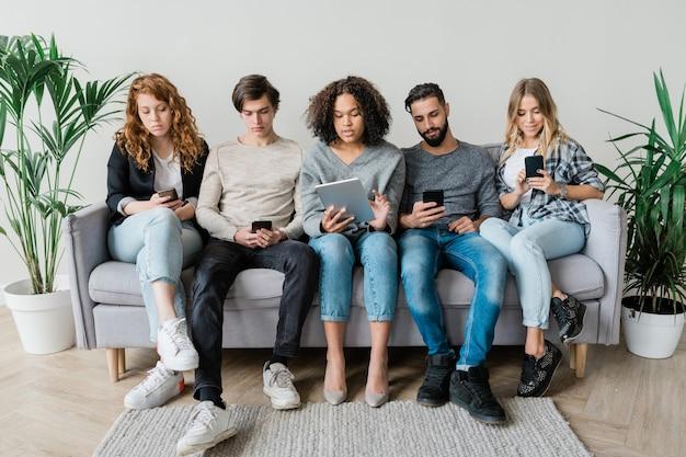 Cinco jovens amigos casuais contemporâneos sentados no sofá, fileira por parede, enquanto usam dispositivos móveis