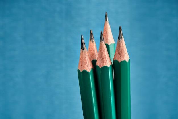 Cinco lápis de grafite idênticos com afiação afiada.