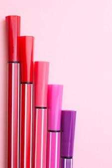 Cinco marcadores ou canetas de cor rosa, roxo, rosa ficam como degraus em um rosa