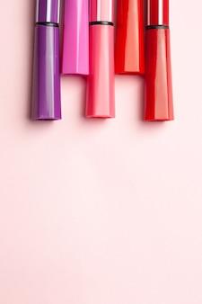 Cinco marcadores ou canetas de cor rosa, roxo, rosa ficam como pontas em um rosa
