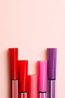 Cinco marcadores ou canetas de cor rosa, roxo, rosa repousam sobre um rosa