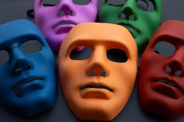 Cinco máscaras faciais em superfície escura.