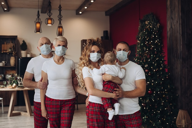Cinco membros da família com um bebê em camisetas e calças com máscaras de proteção no natal em casa.