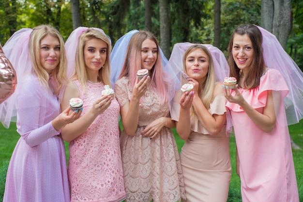 Cinco meninas celebram uma despedida de solteira com bolos nas mãos