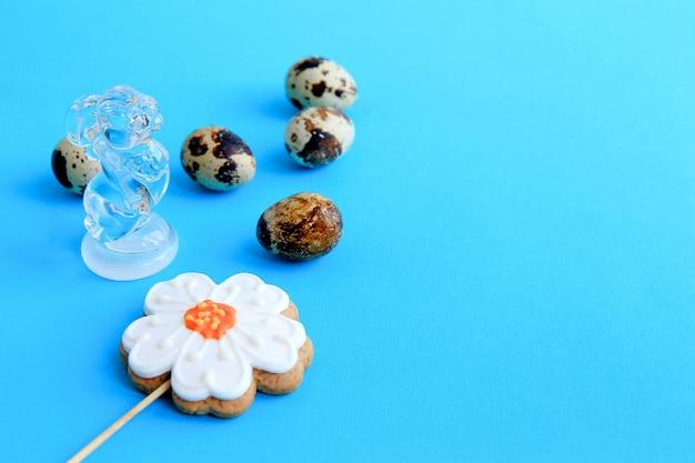 Cinco ovos de codorna em grão e pão de especiarias sob a forma de uma flor e uma estatueta de coelho feita de fundo azul de vidro transparente páscoa vista superior conceito