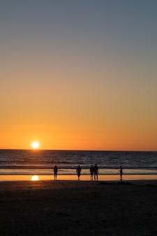 Cinco pessoas caminhando na praia durante a hora dourada