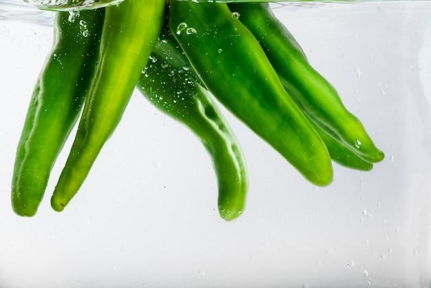 Cinco pimentas jalapeño na água com bolhas.