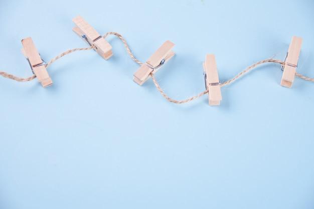 Cinco prendedores de roupa de madeira em uma corda no fundo azul