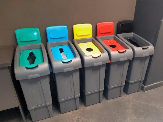 Cinco recipientes coloridos para coletar e separar diferentes tipos de resíduos para reciclagem
