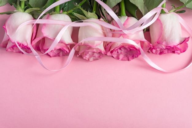Cinco rosas cor de rosa com fita