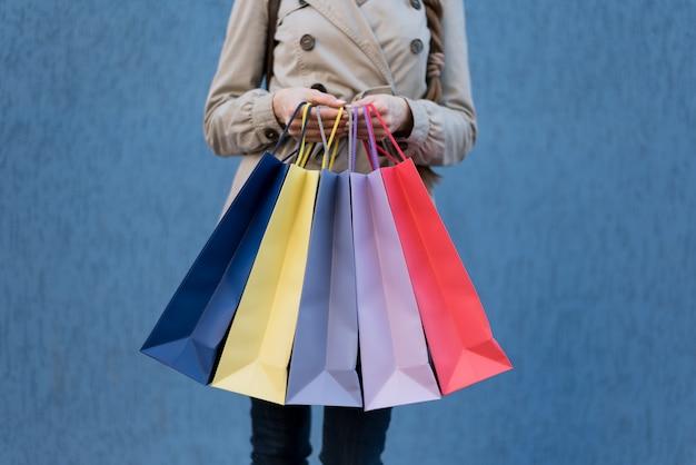 Cinco sacos coloridos para fazer compras em uma mão feminina.