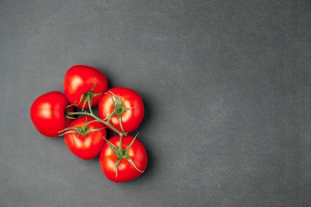 Cinco tomates frescos na superfície de madeira escura, vista superior.