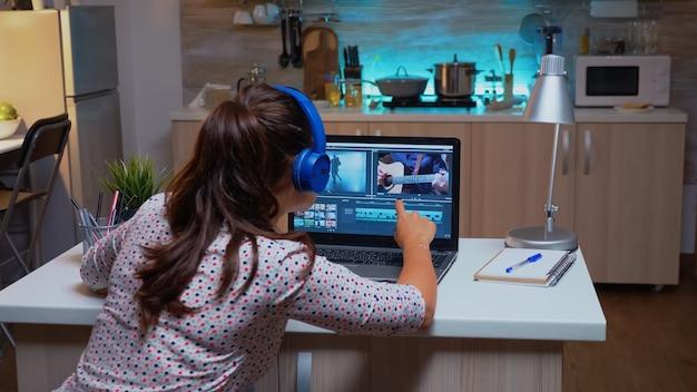 Cineasta editando filmagens durante a noite na cozinha de sua casa. videógrafo criativo trabalhando na montagem de filme de áudio no laptop profissional, sentado na mesa em casa à meia-noite.
