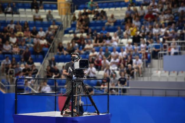 Cinegrafista filma um torneio esportivo internacional com uma câmera profissional