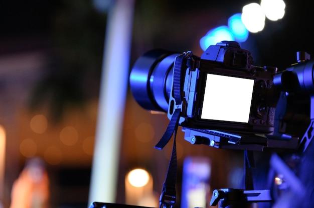 Cinegrafista profissional com câmera no estabilizador do cardan para fazer a produção à noite