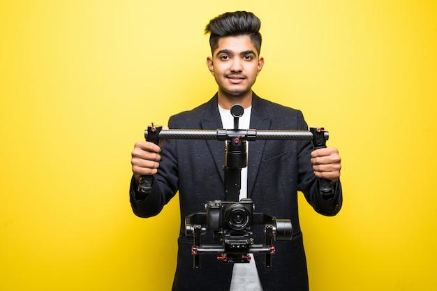 Cinegrafista profissional homem indiano com gimball vídeo slr ronin isolado no fundo do estúdio