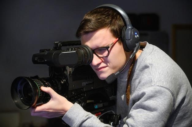 Cinegrafista usando câmera de vídeo digital profissional.
