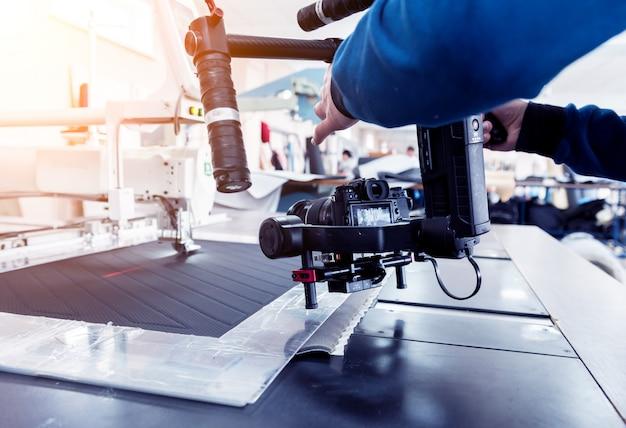 Cinegrafista usando stadicam, fazendo o vídeo da máquina na fábrica de costura