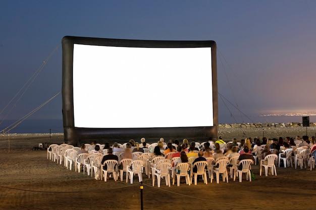 Cinema a céu aberto na praia ao pôr do sol com cadeiras e gente irreconhecível