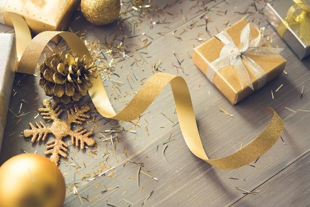 Cintilante caixas de presente de natal com itens de decoração brilhante sobre fundo de madeira