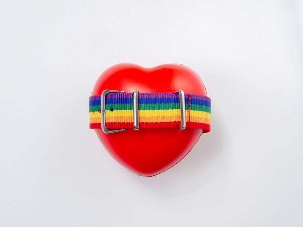 Cinto de bandeira de pequeno arco-íris na bola de coração vermelho, isolada no fundo branco. conceito lgbt com cores do orgulho e faixa da bandeira do arco-íris.