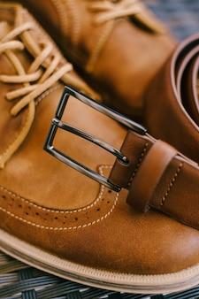 Cinto de couro marrom com fivela de metal nas botas marrons masculinas com atacadores