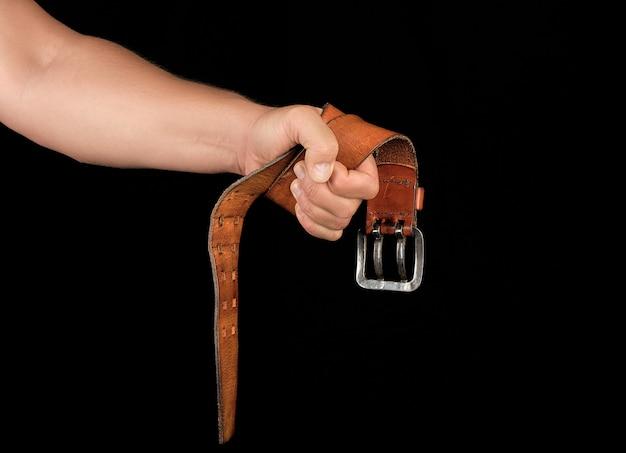 Cinto de couro marrom com uma fivela de ferro em uma mão de homem