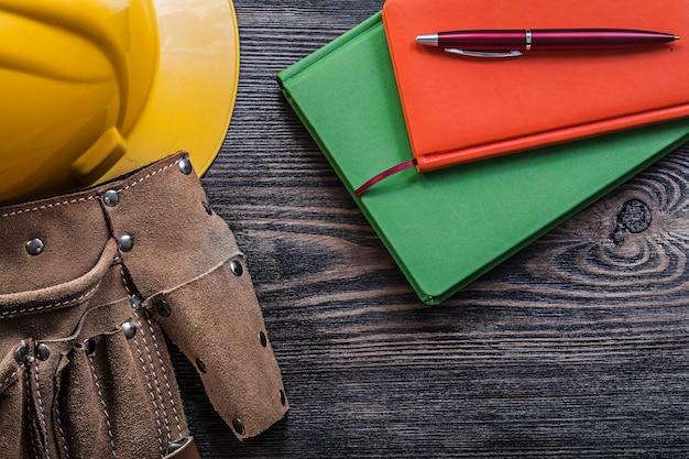 Cinto de ferramentas vazio, capacete, blocos de notas e caneta na placa de madeira