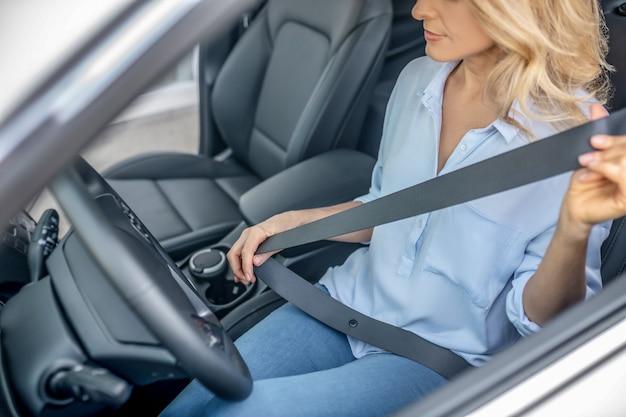 Cinto de segurança. mulher sentada em um carro e colocando um cinto de segurança