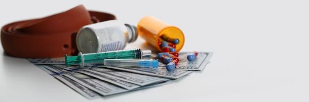 Cinto, dólares, seringas e comprimidos usados