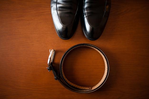 Cinto e sapatos pretos masculinos.